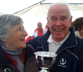 Sue Cassell admires the cup awarded for fifth place, held by President George Black
